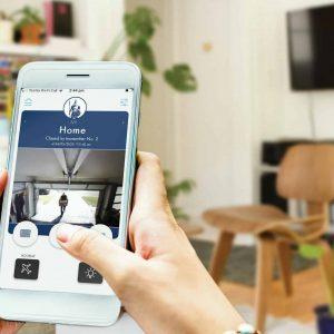 Centurion Garage Doors MY CGD App & Smart Garage Door Camera Opener Open on mobile phone in house with plants and chair